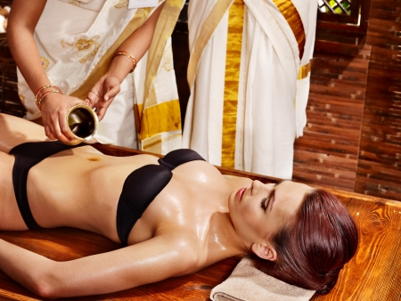ayurvedic: Young woman having stomach Ayurveda spa treatment. Stock Photo