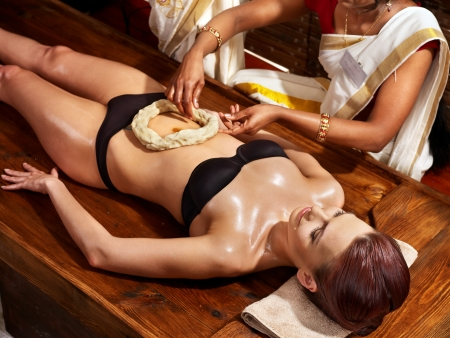 panchakarma: Young woman having stomach Ayurveda spa treatment. Stock Photo