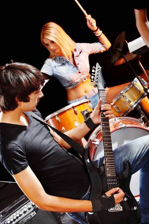 play popular: Musical group playing in night club. Male and female. Stock Photo