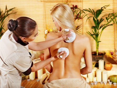 Blond woman getting massage in tropical spa. photo