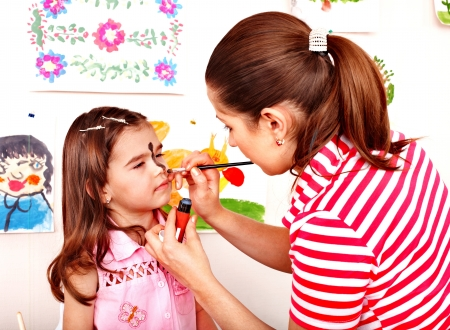 nurser: Child preschooler with face painting. Child care. Stock Photo