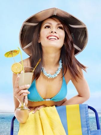 silla playa: Chica en bikini jugo de bebida a trav�s de la paja. Aislado.