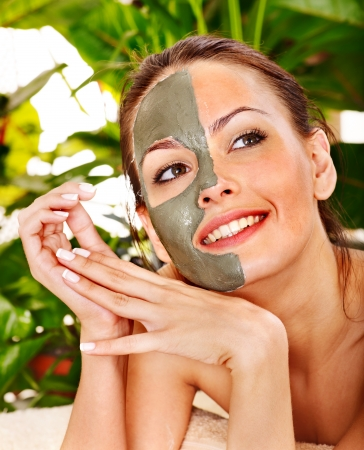 mud girl: Happy woman getting facial mask in tropical beauty spa. Stock Photo