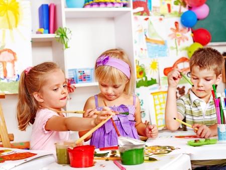 niños pintando: Niño pintura en caballete en la escuela. Maestro ayuda.