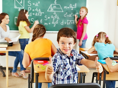 maths: School child with teacher in classroom. Stock Photo