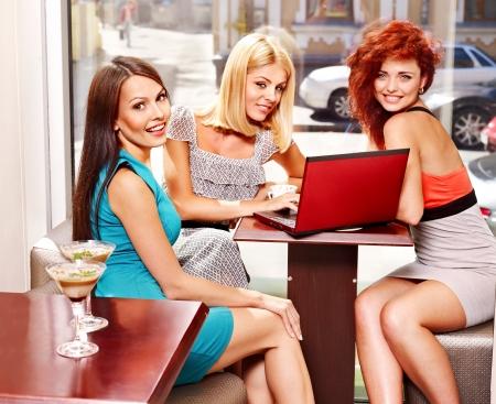vida social: Dos mujeres en cóctel ordenador portátil beber en un café.