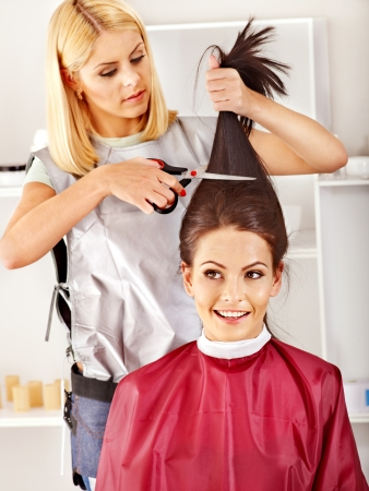 hair curler: Woman at hairdresser with iron hair curler.