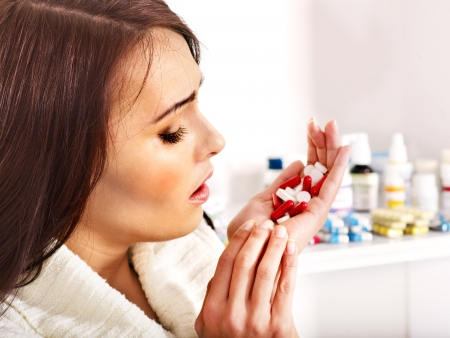 Young woman having pills and tablets. Indoors. Stock Photo