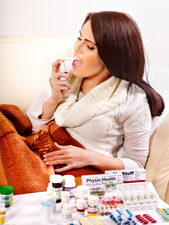 cold remedy: Young woman using throat spray. Indoors