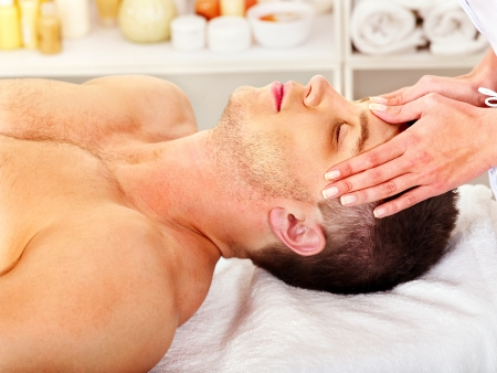 massage face: Man getting facial  massage in beauty spa.
