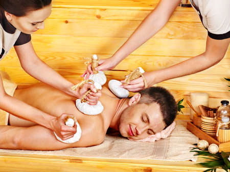 Man getting herbal ball massage treatments  in spa. photo