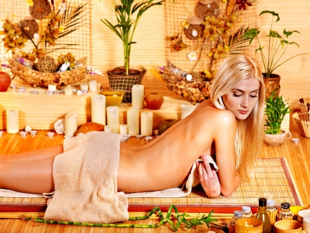 Blond woman getting herbal ball massage in spa. photo