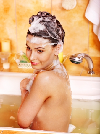 hair shampoo: Woman washes her head at home bathroom.