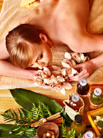 Woman getting herbal ball massage treatments  in spa. photo
