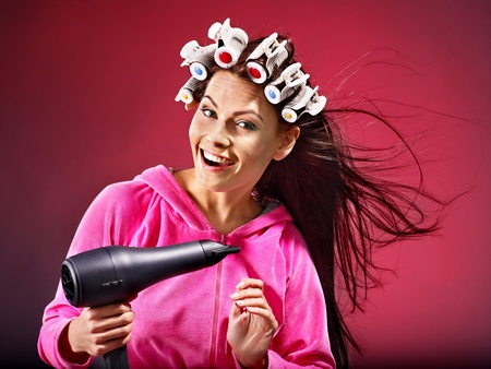 Happy woman wear hair curlers holding  hairdryer.