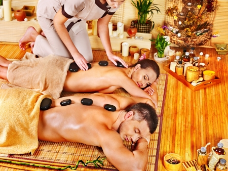 day spa: Woman and man getting stone therapy massage in bamboo spa. Stock Photo
