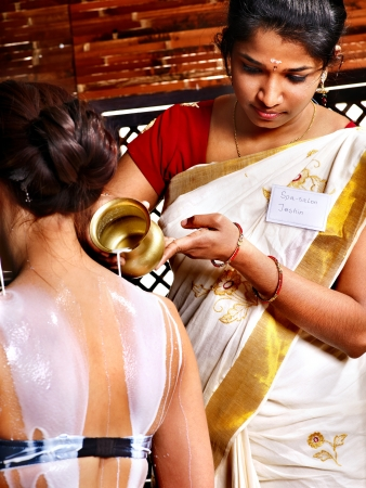 panchakarma: Woman having Ayurvedic spa treatment. Pouring milk.