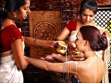 window treatments: Woman having Ayurvedic spa treatment. Pouring milk.