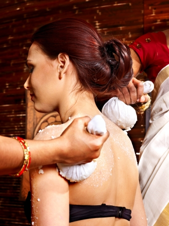 panchakarma: Woman having ayurvedic massage with pouch of rice.