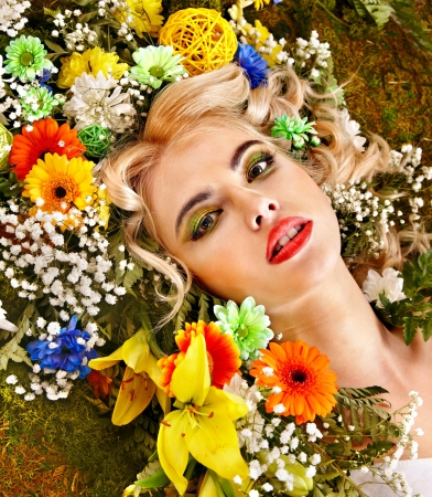 Woman with flower hairstyle lying on grass. Art photo. photo