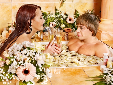 Glasses of champagne and candles: Couple relax at luxury spa with flower.