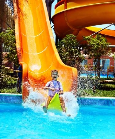 bikini wear: Child on water slide at aquapark  Summer holiday  Stock Photo