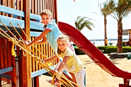 Happy children move out to slide in playground. photo