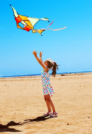 Child flying kite beach outdoor. Stock Photo