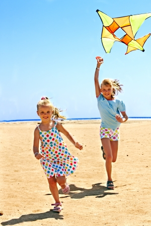 kids playing water: Child flying kite beach outdoor. Stock Photo