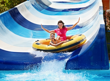 amusement park ride: Child with mother on water slide at aquapark. Summer holiday.