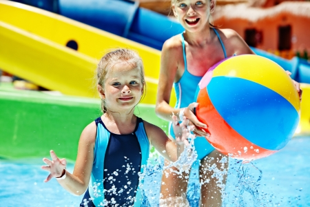 ball on water: Little girl on water slide at aquapark. Stock Photo