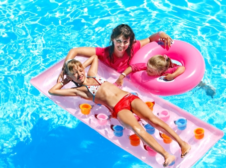 beach wear: Family with children in swimming pool. Summer outdoor.