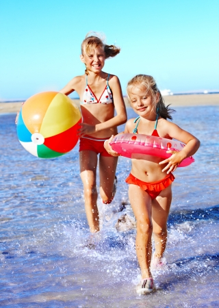 Children holding hands running on  beach. Stock Photo - 18636182