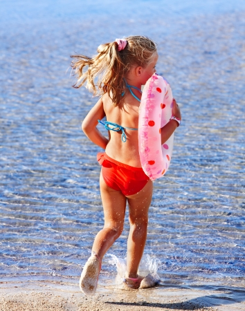 Child running on the beach in water. Rear view. photo