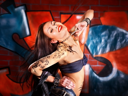 body art: Woman with body art aganist graffiti brick wall.