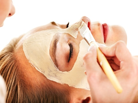 Woman with clay facial mask in beauty spa. Isolated. photo