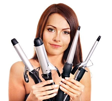curling irons: Young woman holding iron curling hair. Isolated.