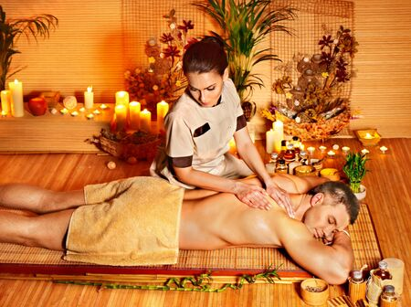 bamboo therapy: Man getting massage in bamboo spa. Female therapist.