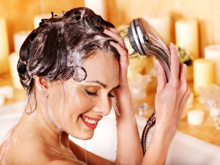 Woman washes her head at home bathroom. photo