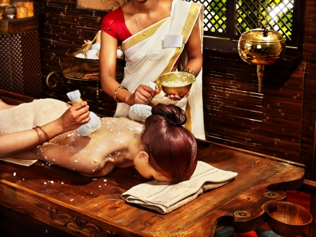 Woman having ayurvedic massage with pouch of rice. Stock Photo - 18664800