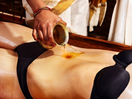 belly button: Young woman having stomach Ayurveda spa treatment. Stock Photo