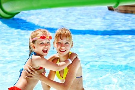 Ni?os en la diapositiva de agua en parque acu?tico. Vacaciones de verano.