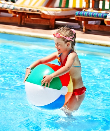 ball on water: Little girl  playing ball in swimming pool. Stock Photo