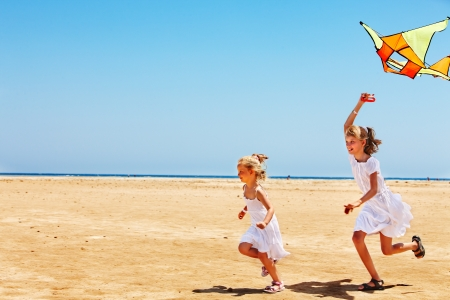 playing in the sea: Child flying kite beach outdoor. Stock Photo