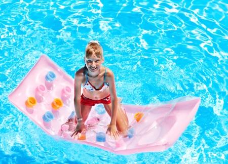Child swimming on inflatable beach mattress. photo