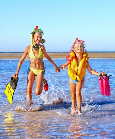 Happy children with flippers running on  beach. photo