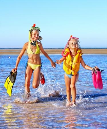 flippers: Niños felices con aletas que se ejecutan en la playa.