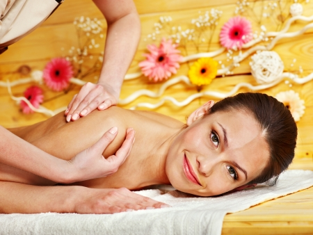 natural therapy: White woman getting  massage in wooden spa.