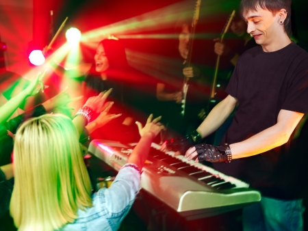 Musical group male and female  performance in night club.