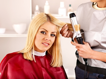 curler: Woman at hairdresser with iron hair curler.